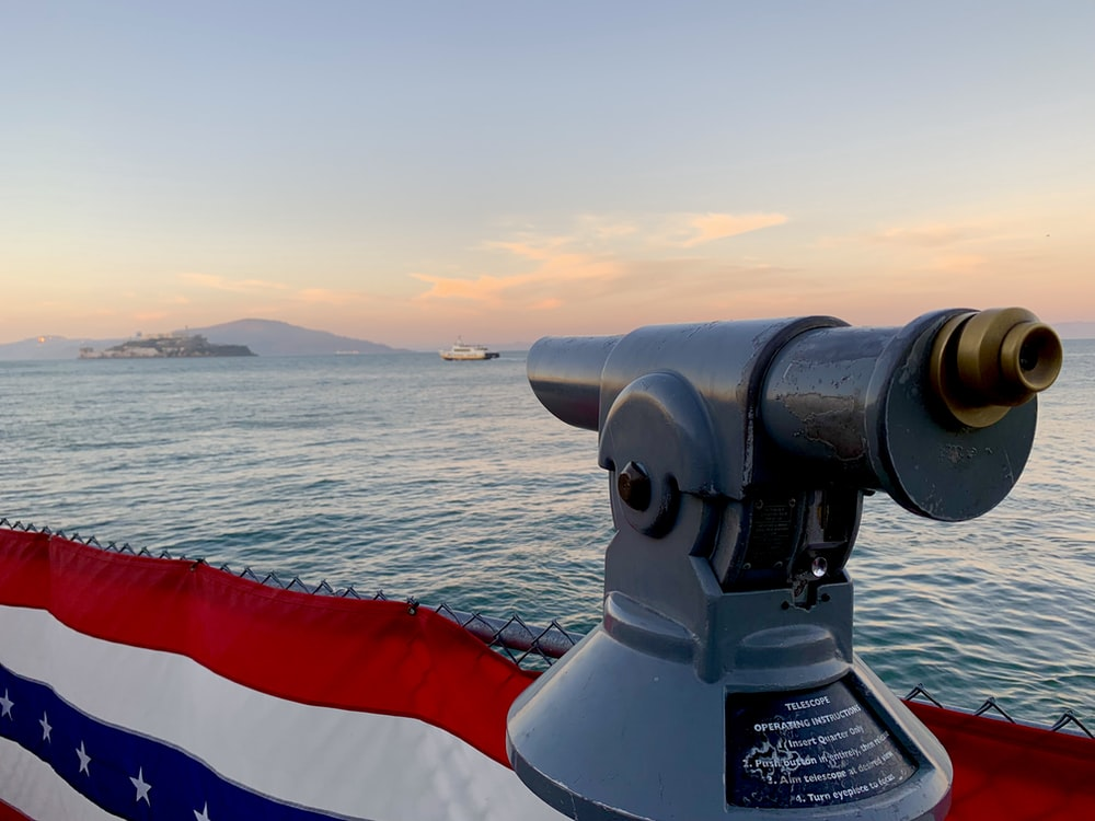 gray telescope near American flag viewing blue sea and mountain under blue and white sky