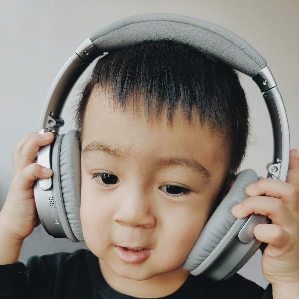boy wearing grey cordless headphone