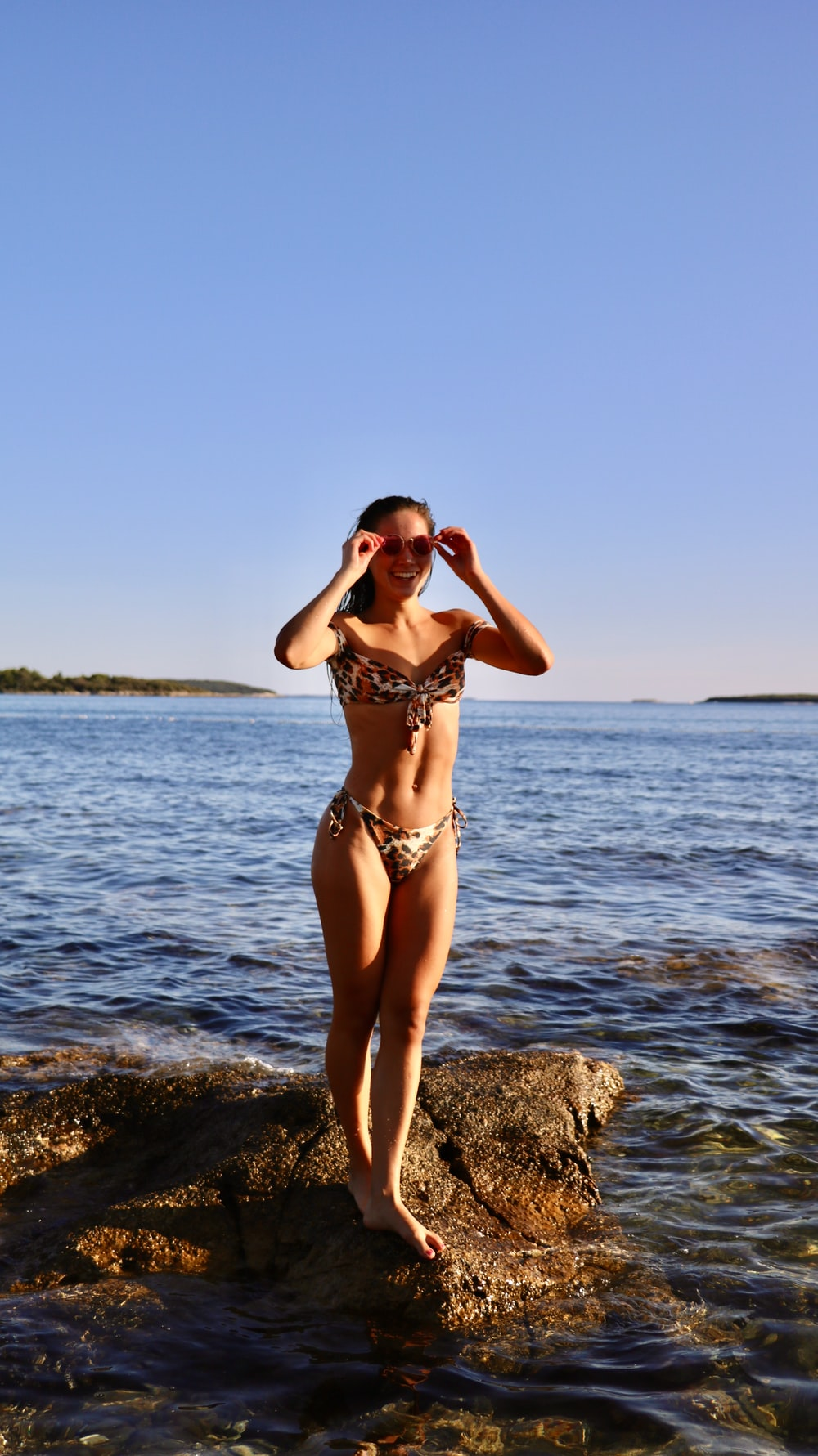woman wearing bikini while standing on the stone near the body of water