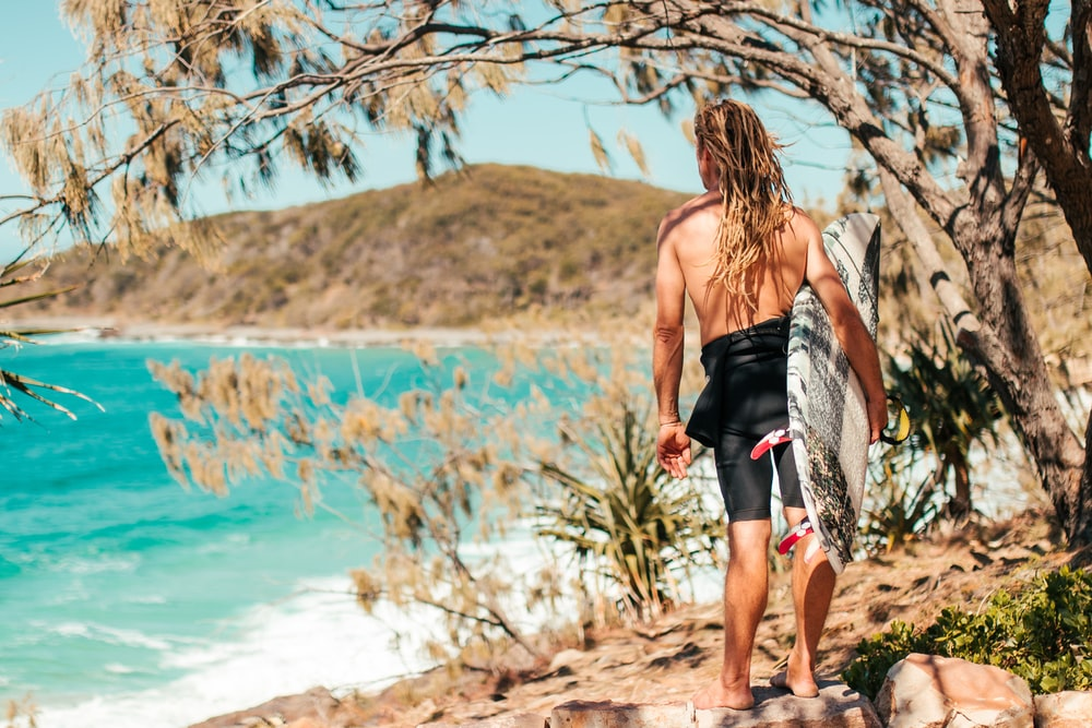 topless man holding surfboard while standing near body of water viewing mountain