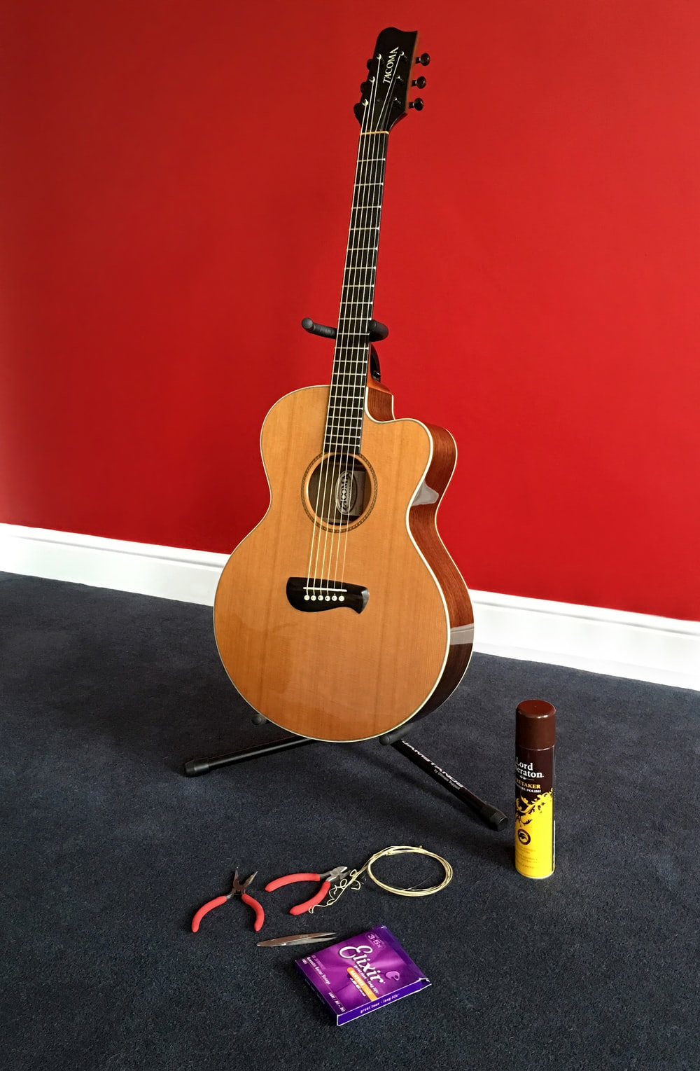 brown acoustic guitar near red handled pliers and spray can