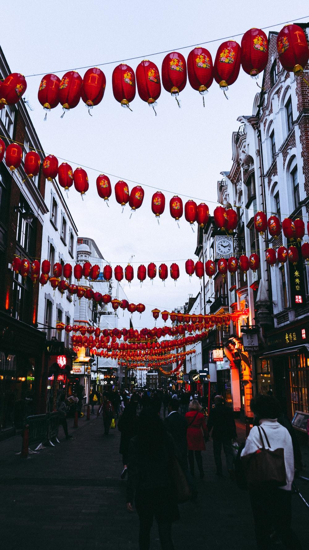 people walking between buildings under hanging Chinese lanterns during day