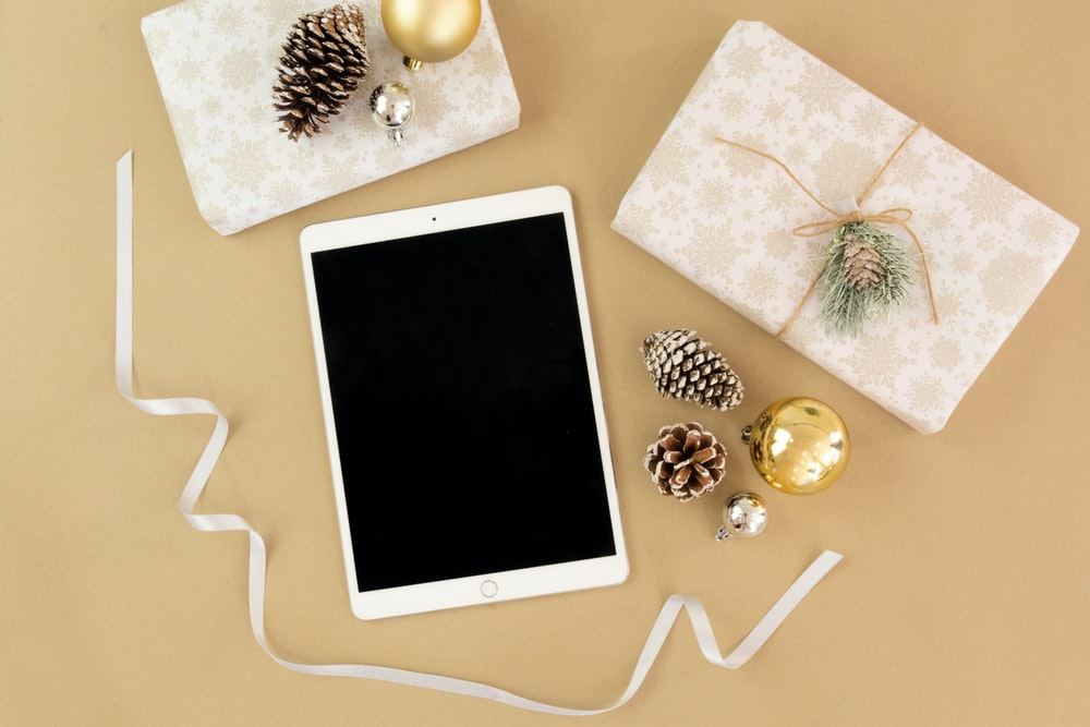 gold iPad near brown pinecone, gold bauble, white ribbon, and beige gift box