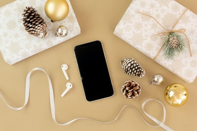 flat lay photography of android smartphone and airpods decorations teams background
