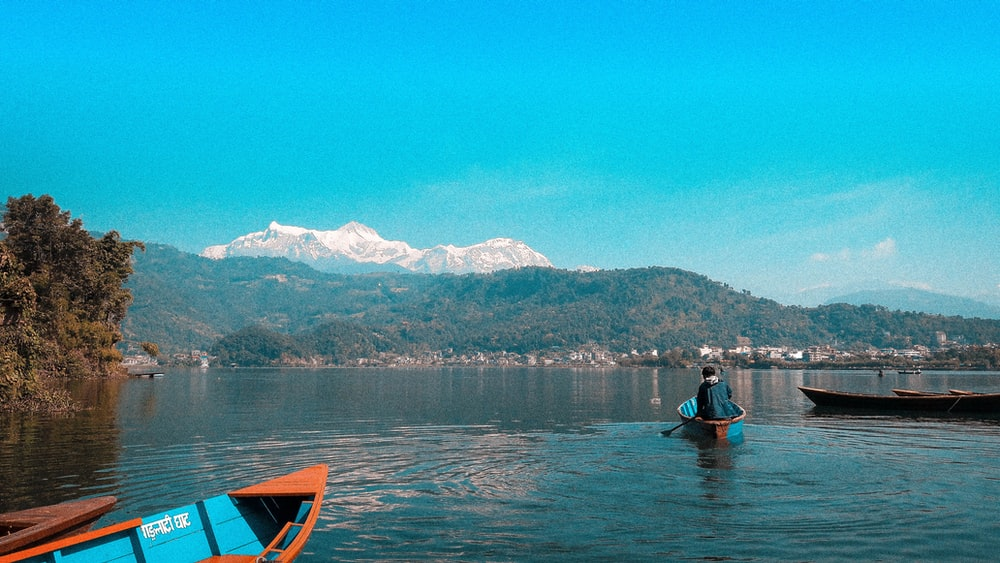person riding on blue boat on body of water viewing mountain under blue and white sky