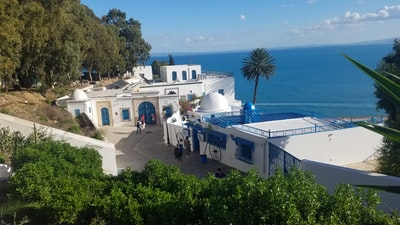 people near white and blue seaside resort viewing blue sea under blue and white sky tunisia teams background