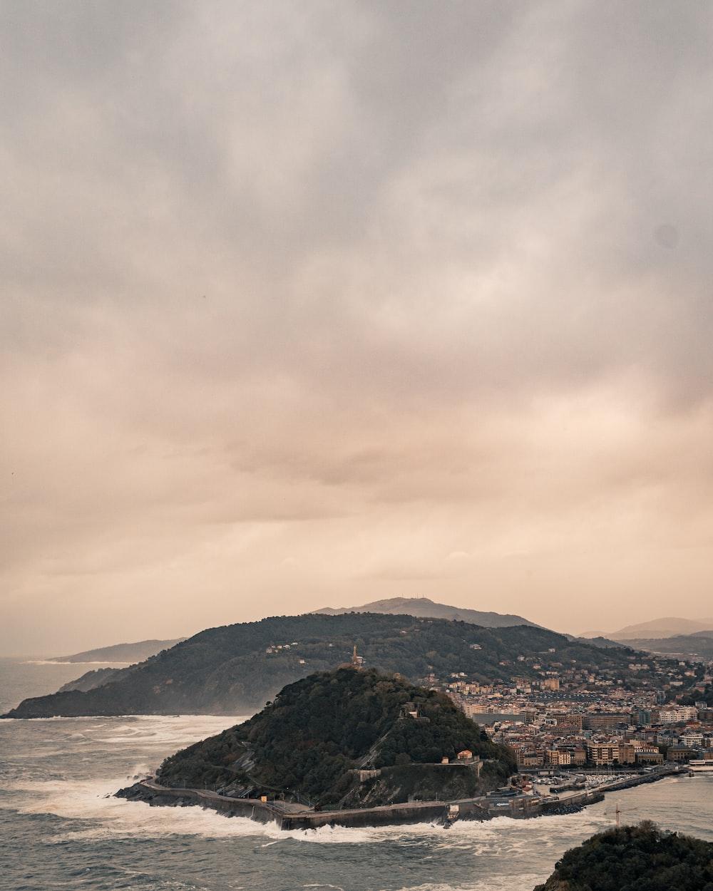 houses beside sea and mountain