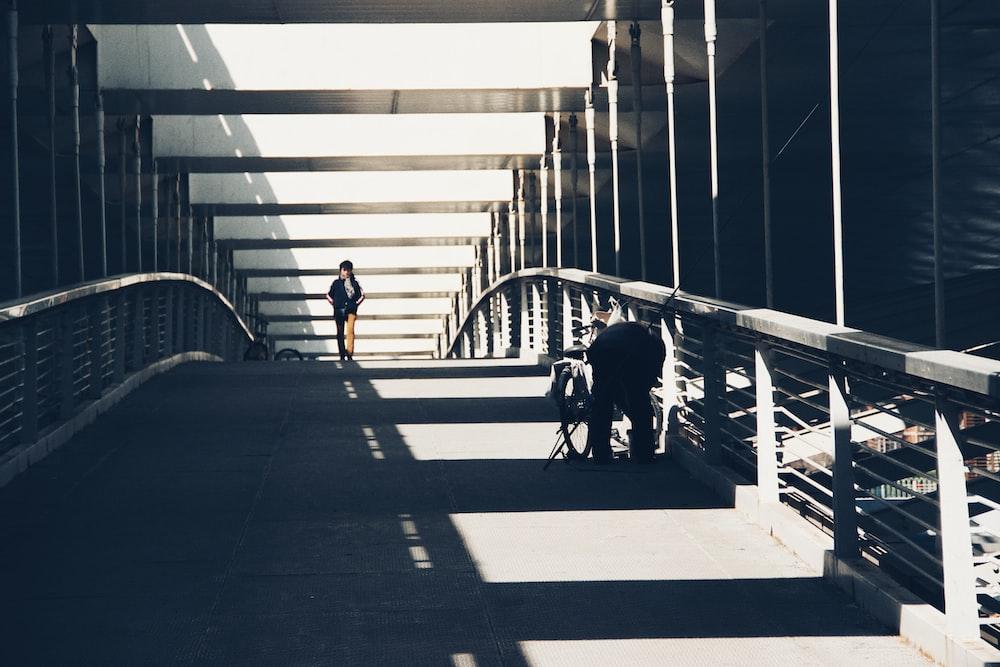 person walking in bridge during daytime