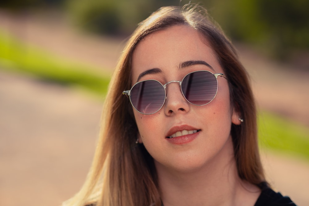 shallow focus photo of woman in black sunglasses with silver frames