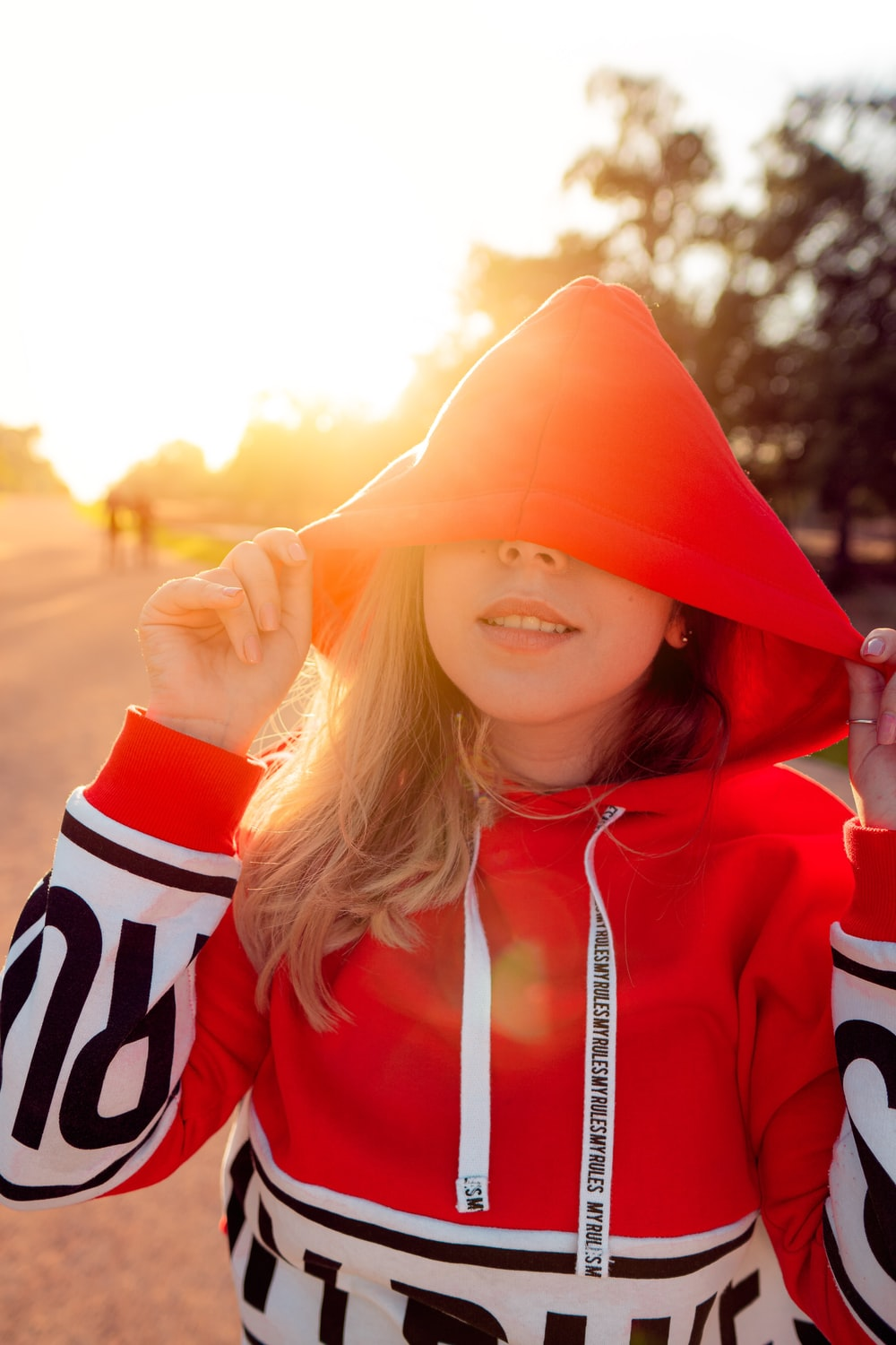 woman wearing red and white pullover hoodie during sunrise