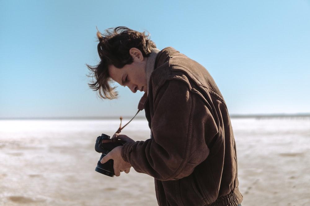 man wearing brown jacket holding DSLR camera