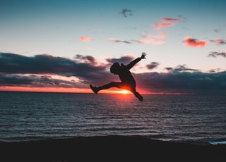 silhouette of a man jumping in front of the sun