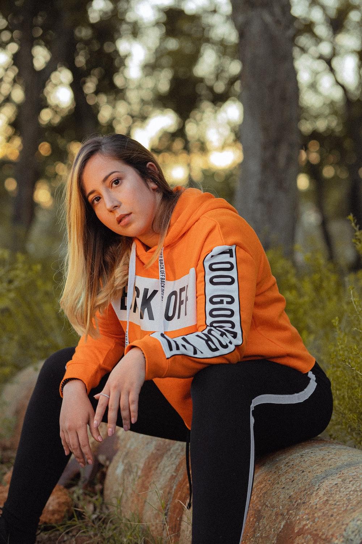 woman sitting on log in orange hoodie