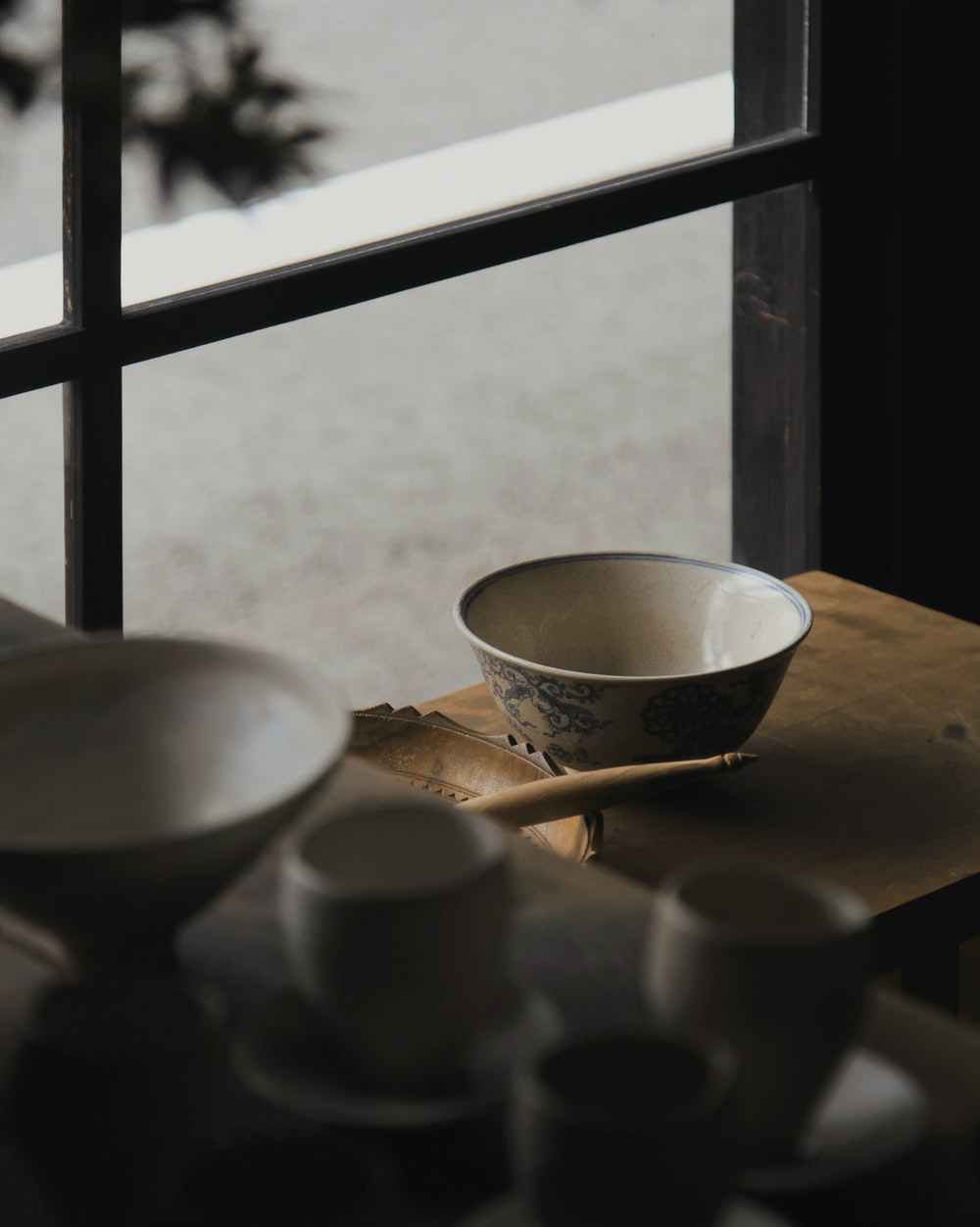 round white and blue ceramic bowl on wooden table near glass window