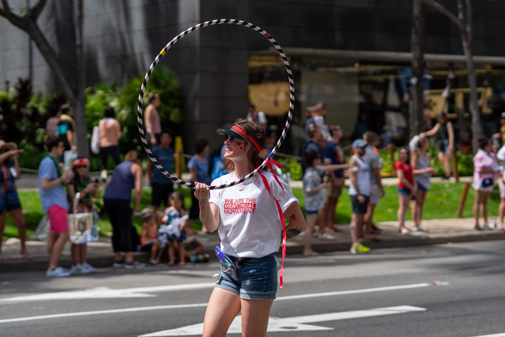 woman wearing white and red crew-neck t-shirt and sunglasses standing while holing hula hoop