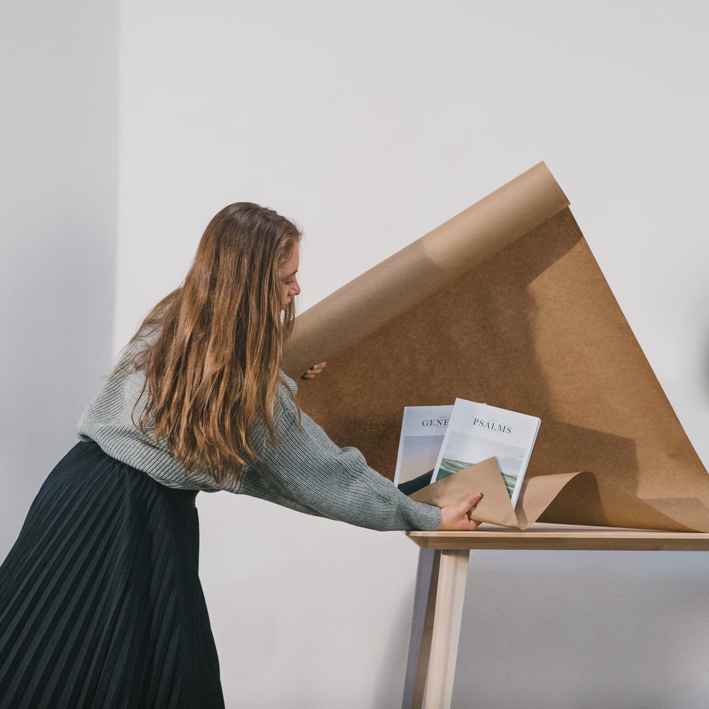 woman wrapping books on table