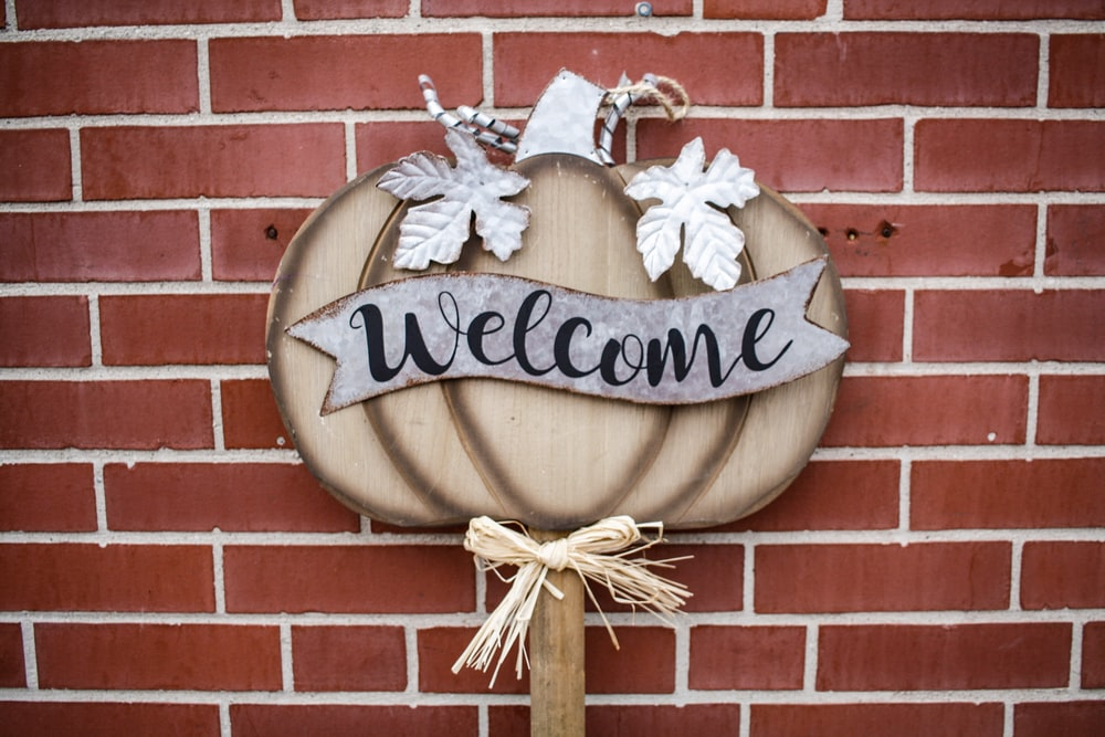 brown and gray pumpkin with welcome text sign