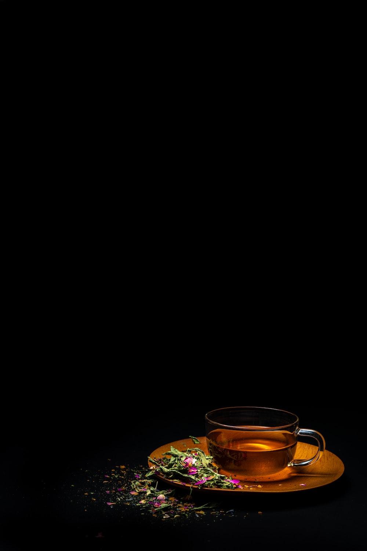 clear glass teacup on saucer