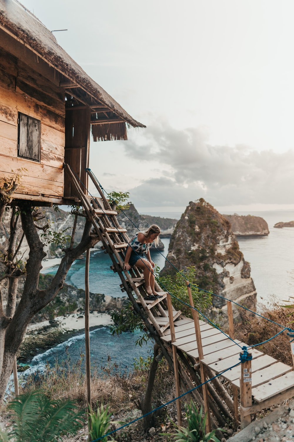 woman stepping and going down on stairs viewing mountain and body of water