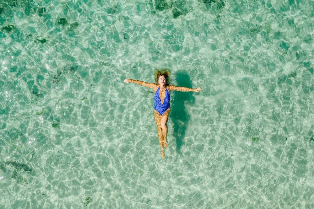 woman wearing blue one-piece bikini on the body of water