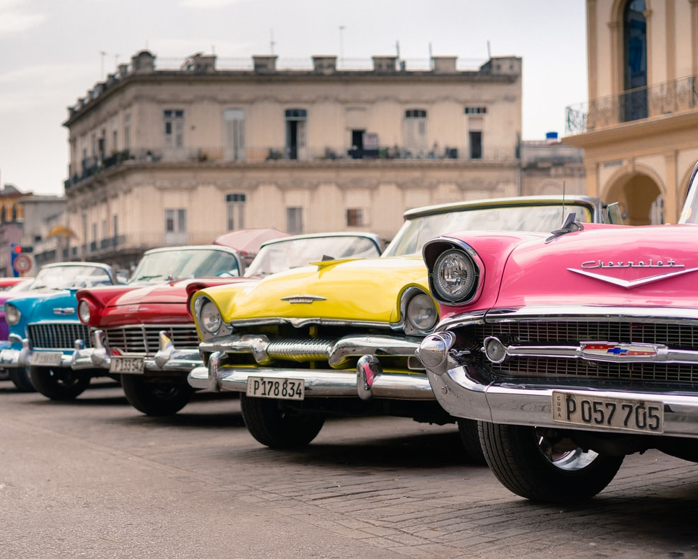 assorted-colored antique cars parking near road