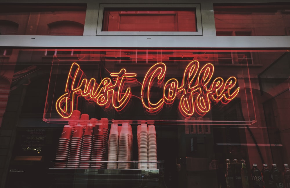Just Coffee neon sign at night