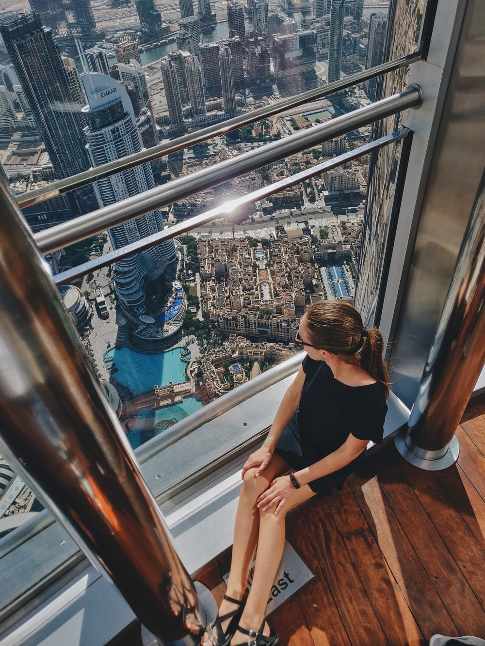 woman sitting beside window glass building