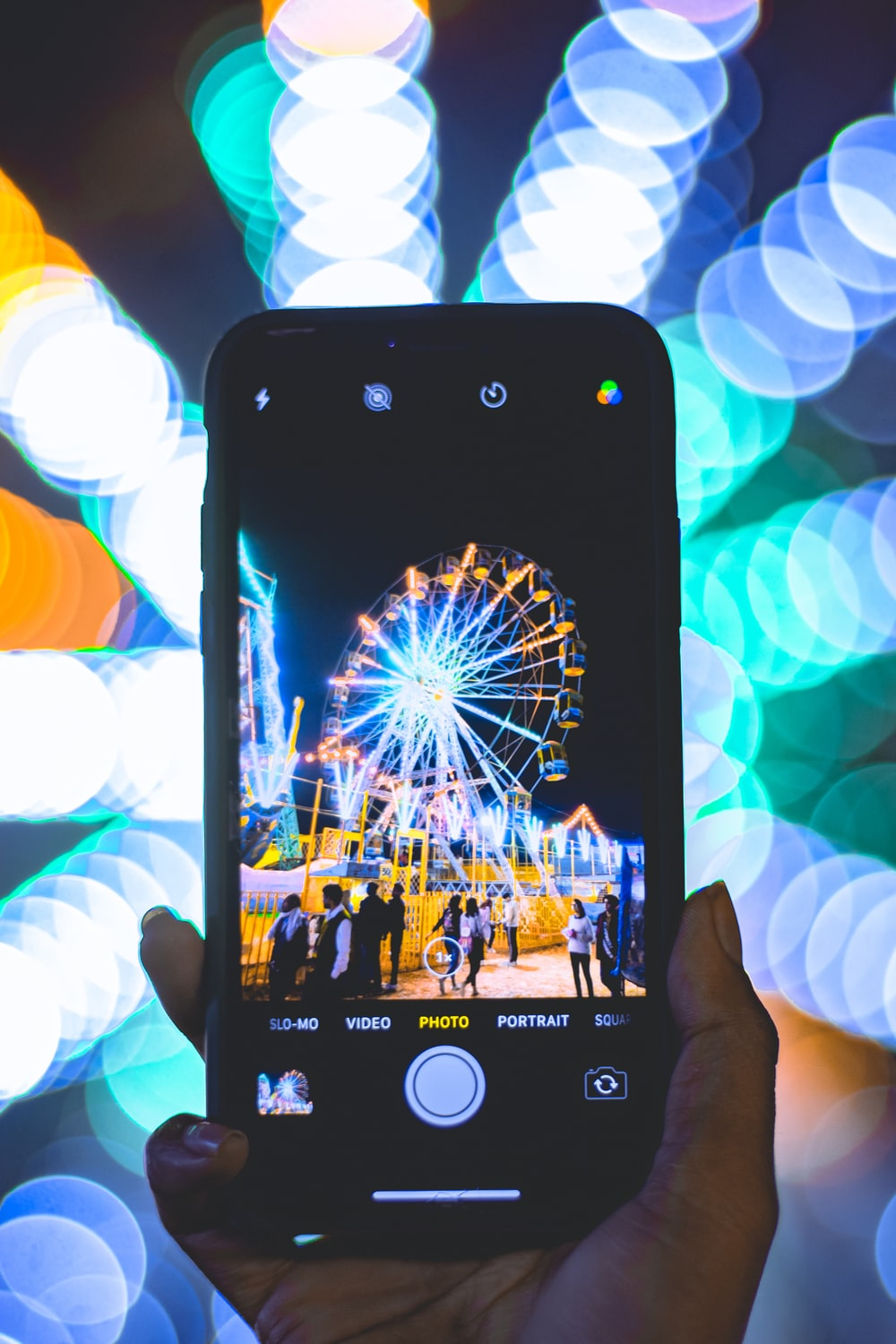 shallow focus photo of person taking photo of Ferris wheel using smartphone