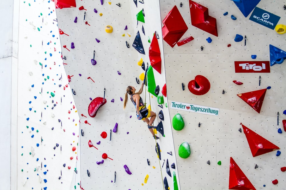 photography of woman doing wall climbing during daytime