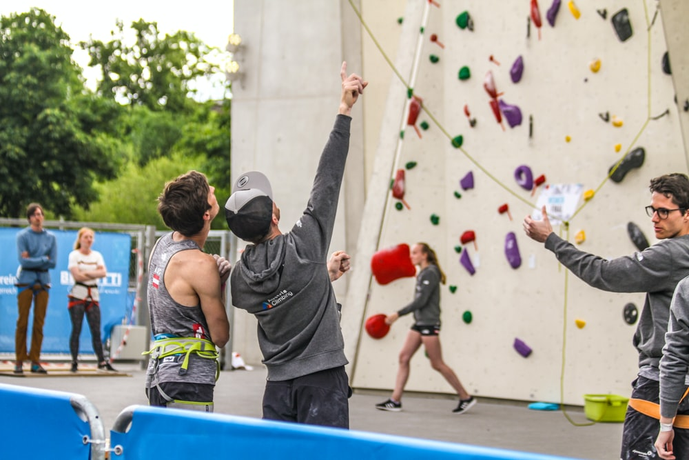 people standing beside rock climbing wall
