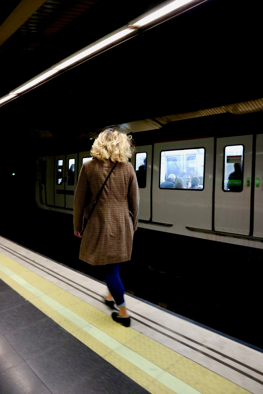 woman wearing brown coat standing near train