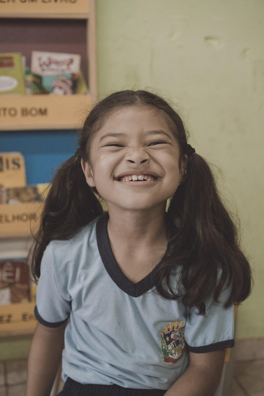 smiling girl sitting near shelf