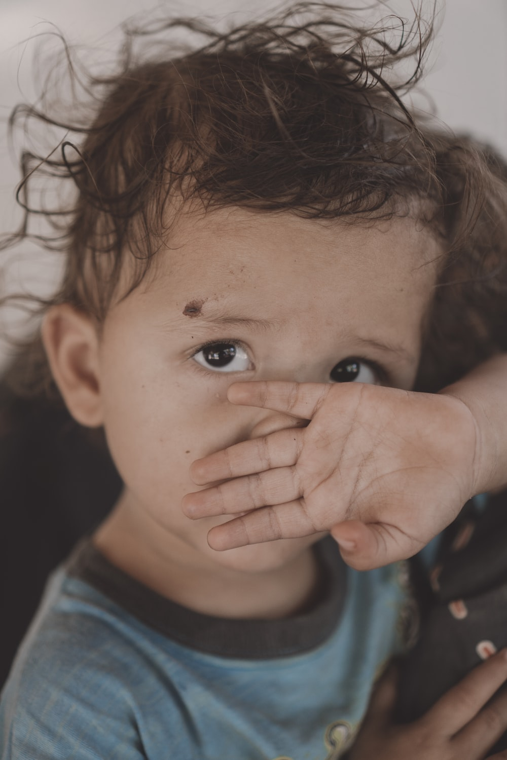 toddler covering their nose and mouth with their hand