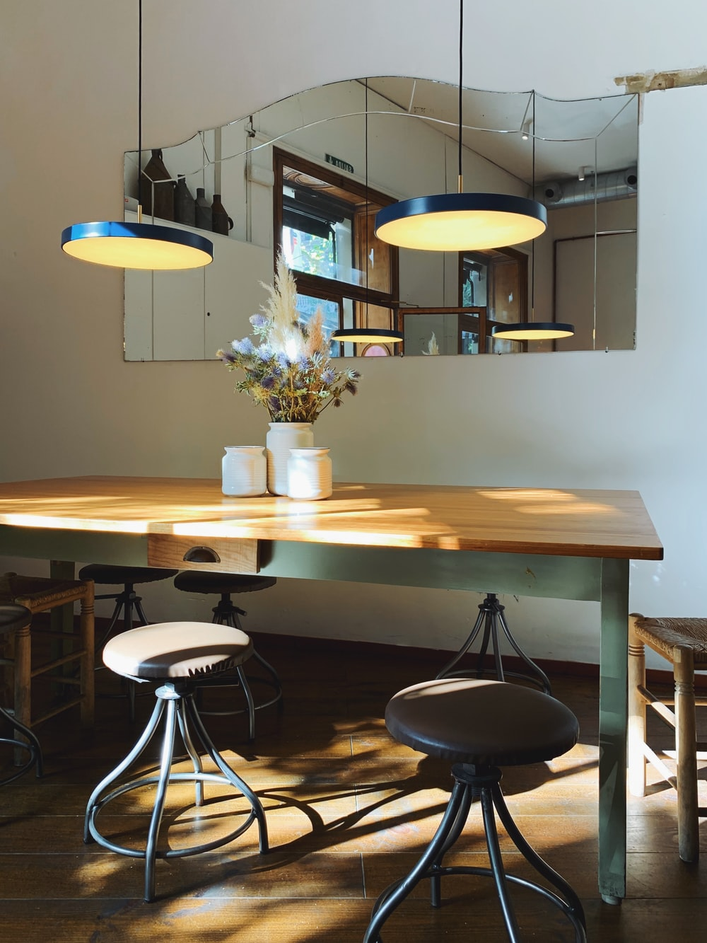 empty dining set with turned on pendant lamps