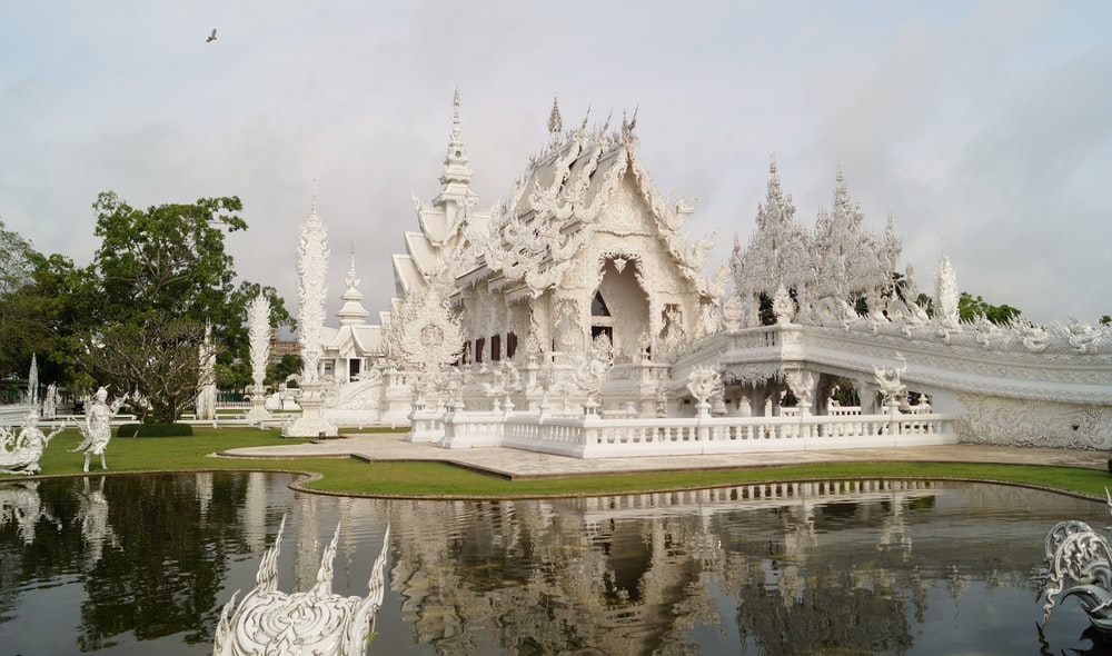 white concrete cathedral near body of water