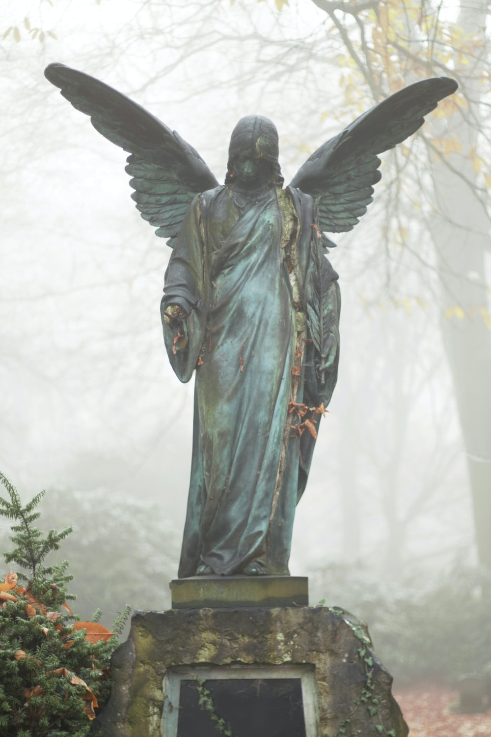 angel in gray robe statue during daytime