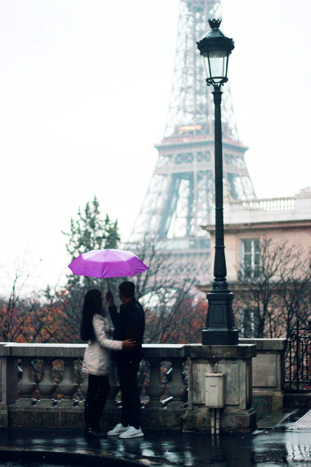 man and woman holding umbrella standing beside railing