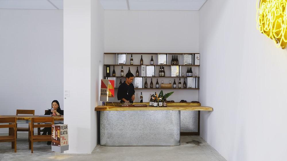 man standing in mini bar room