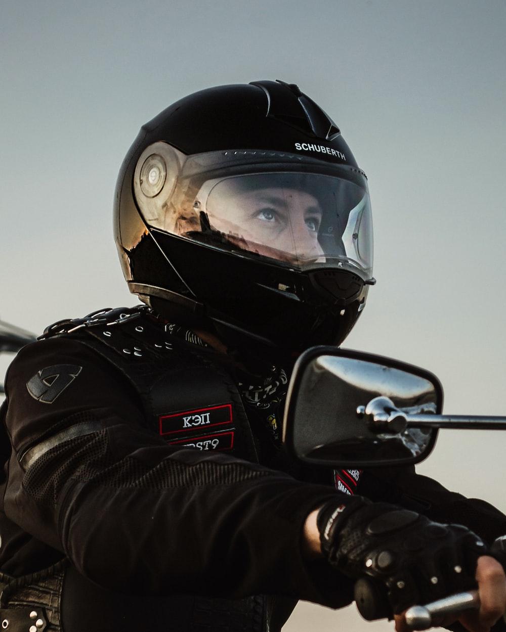 man wearing black helmet riding on motorcycle