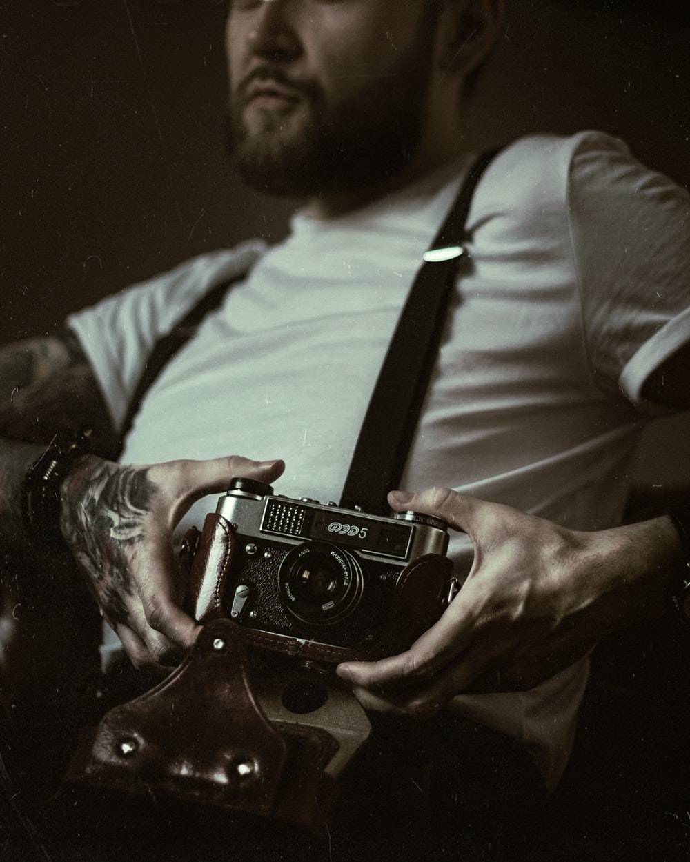 man in white crew-neck top holding black DSLR camera