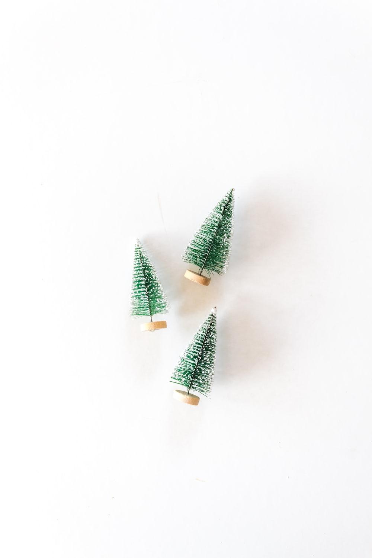 three pine tree miniatures on white surface