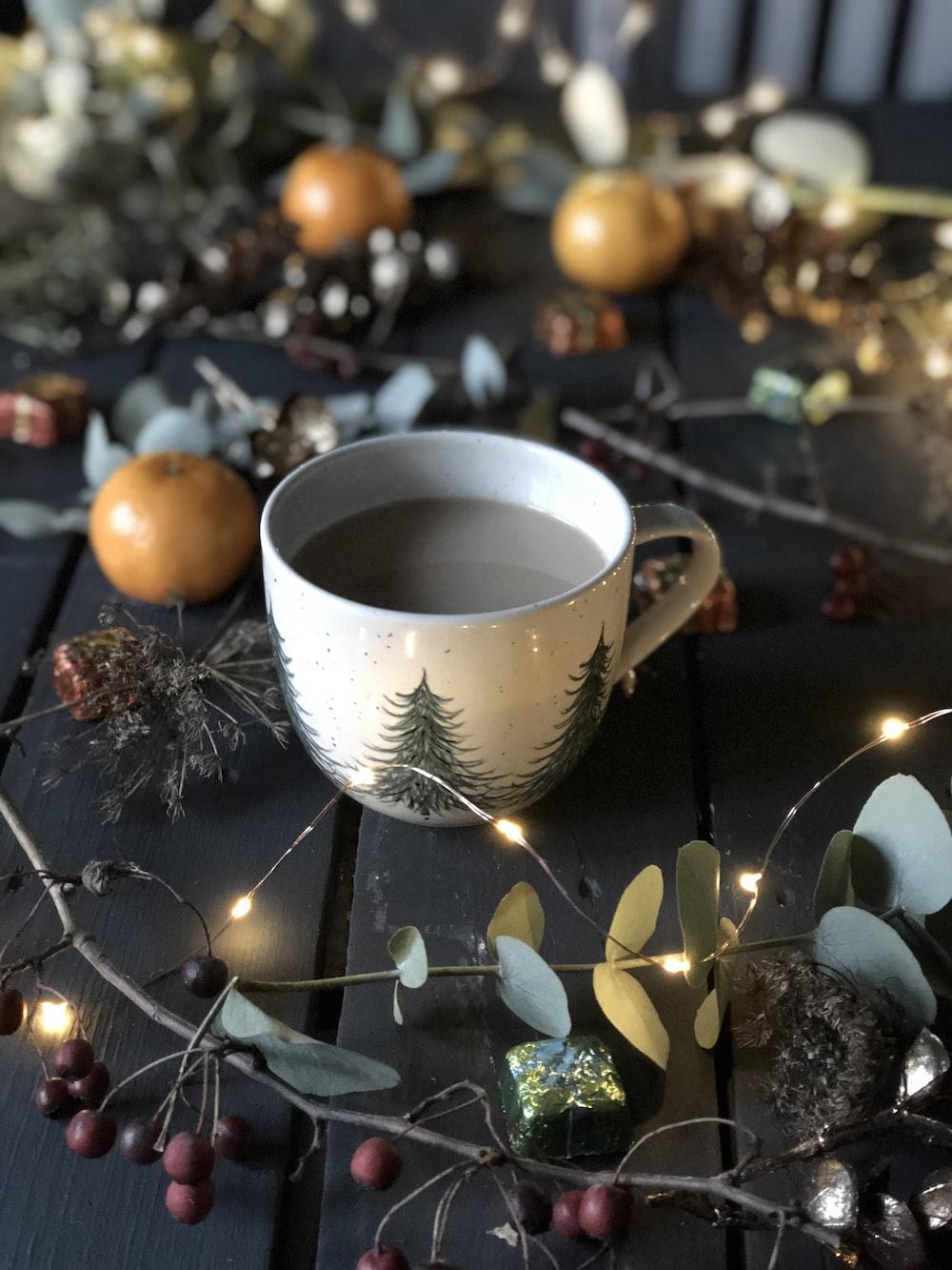 white teacup beside string lights