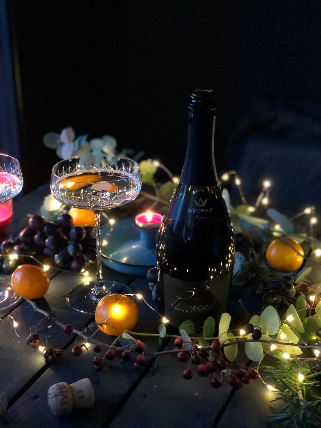 A bottle of Prosecco and a coupe on a sparkling decorated Christmas table