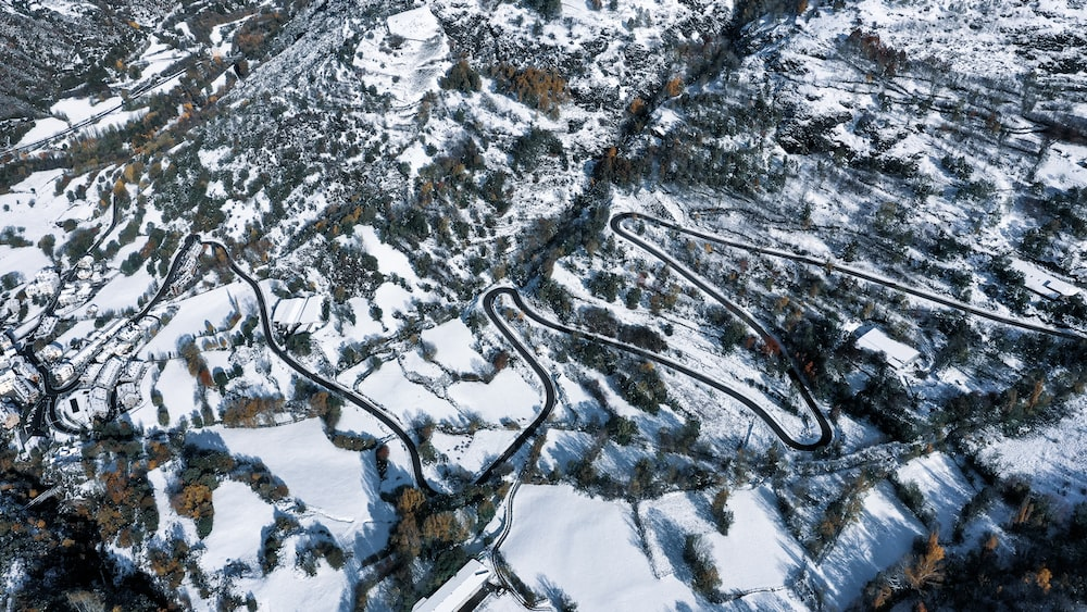 aerial photography of curved road covered with snow during daytime