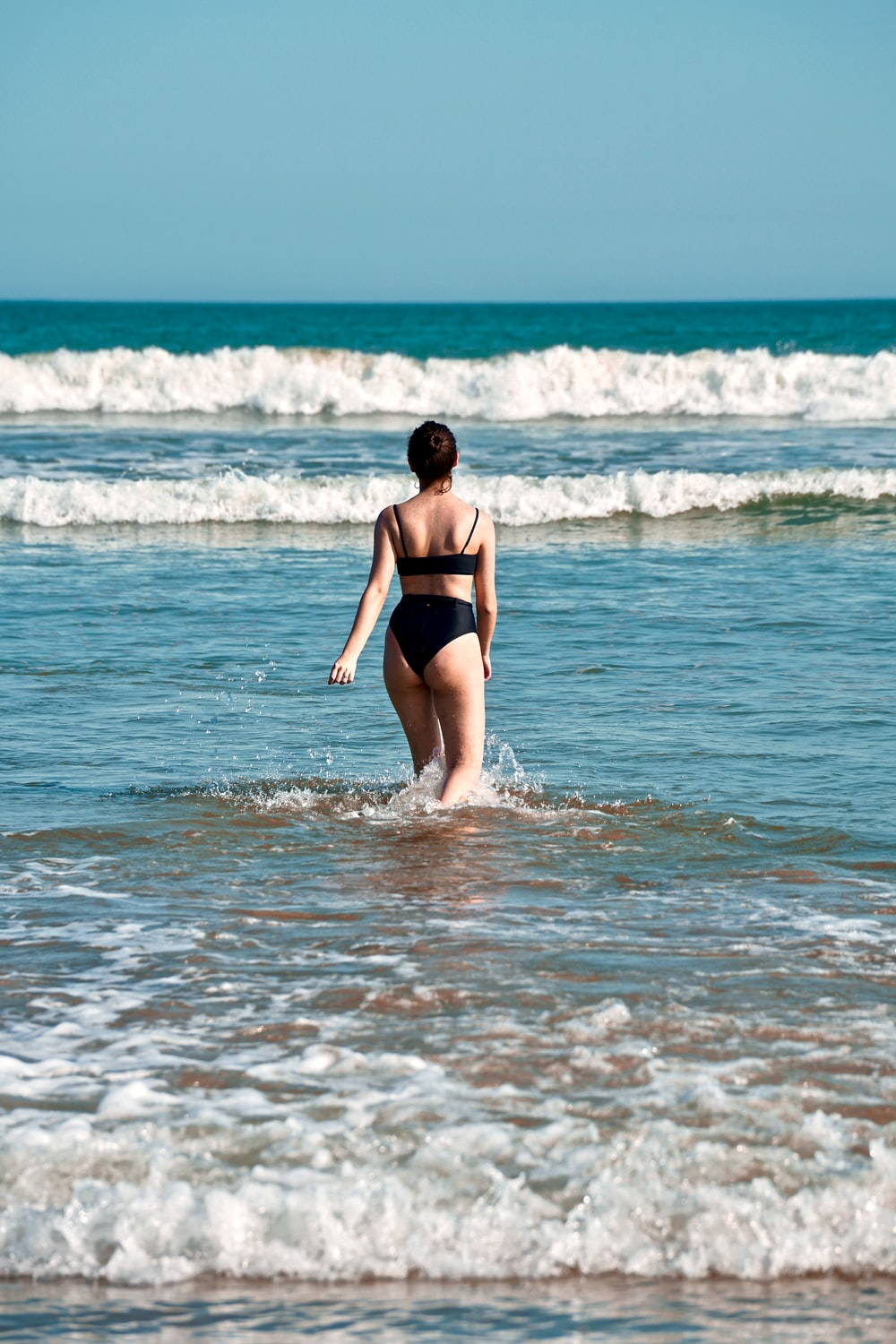 woman wearing black bikini set walking going on blue sea