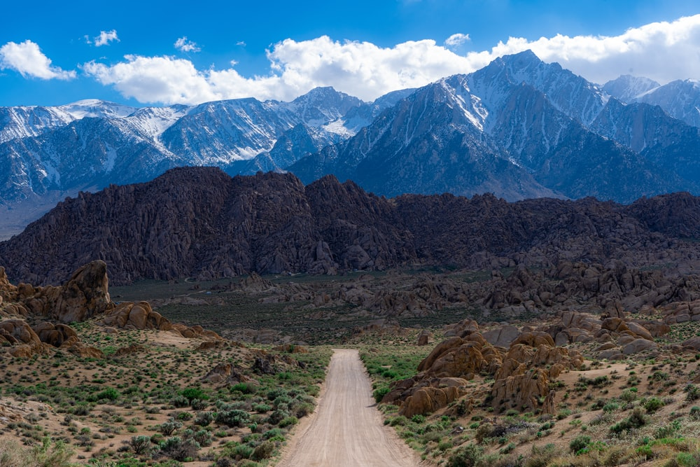 dirt road in the middle of the field near mountains