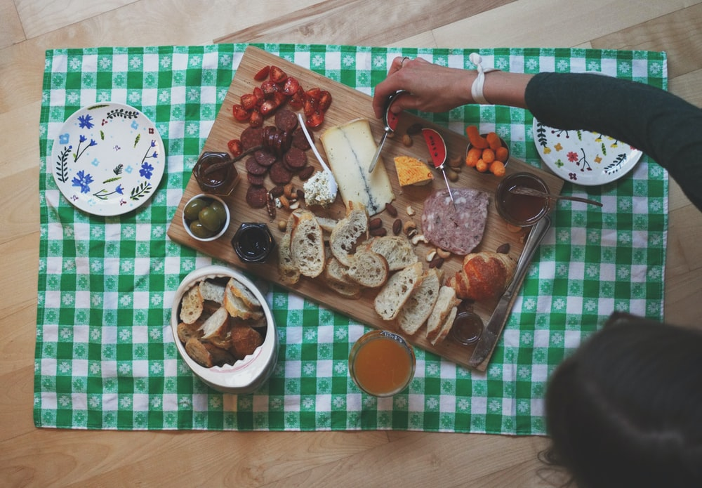 woman about to slice the cheese on wooden board surrounded with bread and sausages