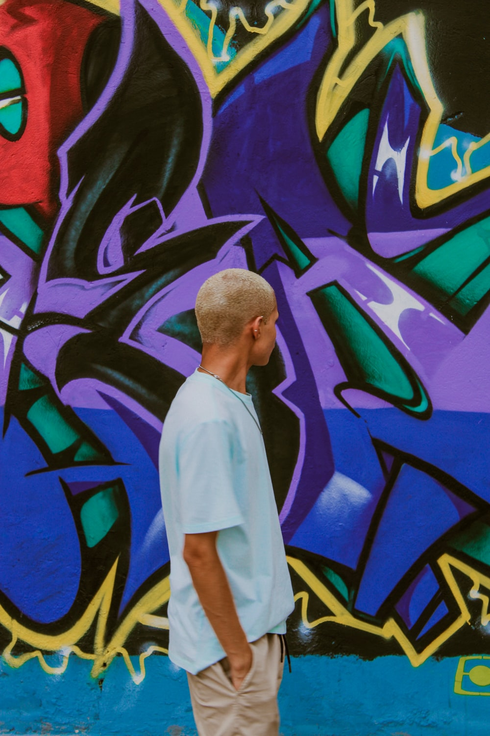 man looks and stands in front of the graffiti wall