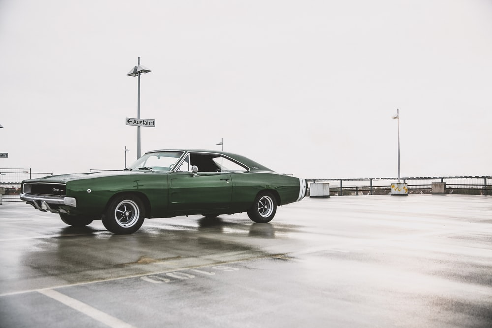 green muscle car at the wet parking lot
