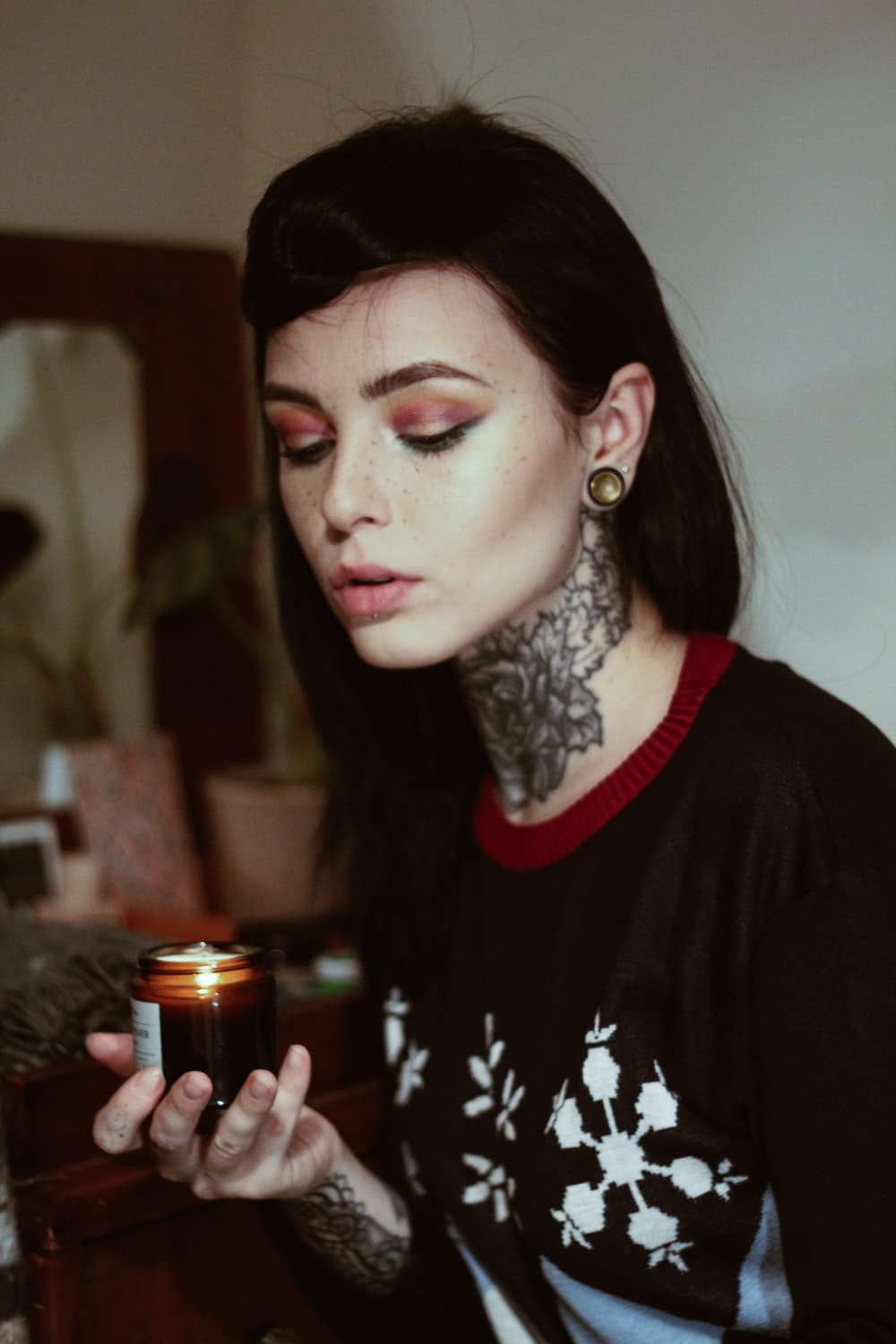 woman wearing black, white, and red floral crew-neck t-shirt holding lighted tealight candle